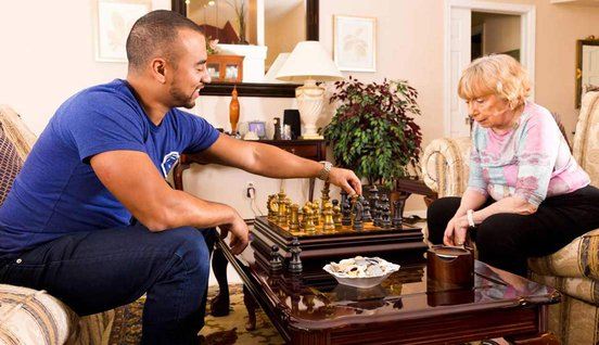 Photo of senior playing chess with a Papa Pal