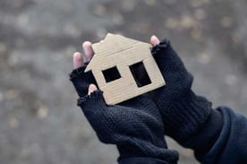 Homeless Person Holding Cardboard House Cutout