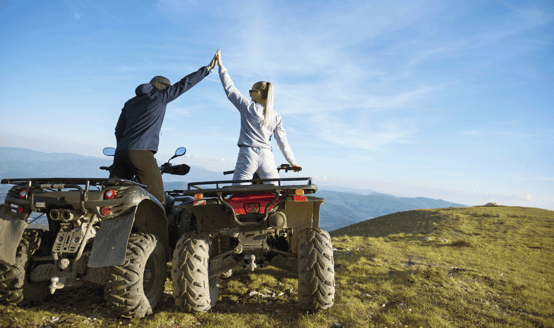 Photo of a couple riding ATVs