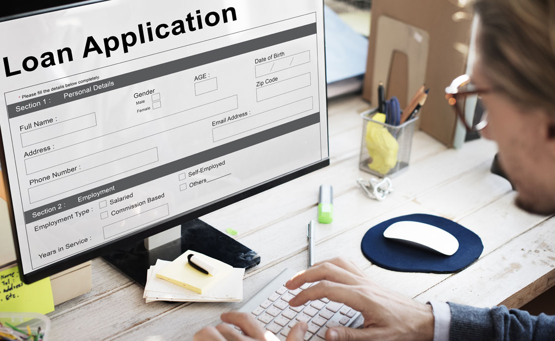 Photo of a man filling out an online loan application