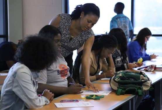 An image of a Credit Abuse Resistance Education (CARE) volunteer helping students