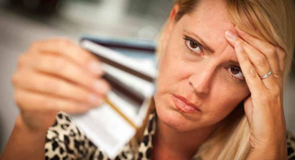 Image of a woman looking frustrated with her credit cards.
